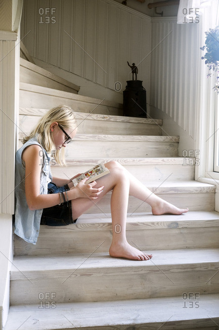 Sweden, Skane, Vejbystrand, Girl reading book on wooden steps at home