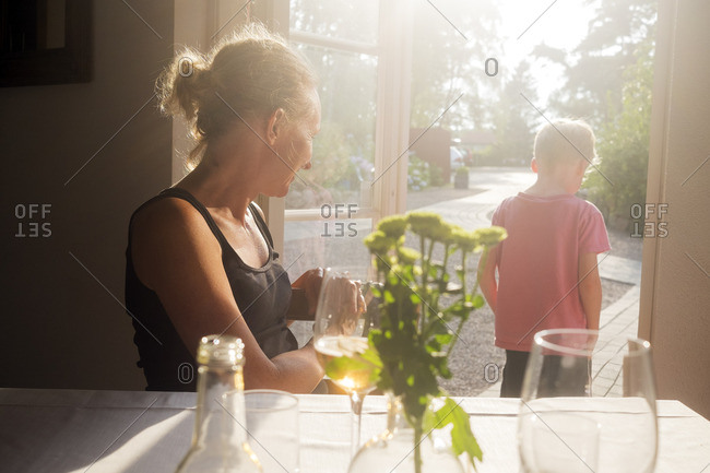 Sweden, Skane, Kullaberg, Mother looking at son standing in doorway to backyard at restaurant