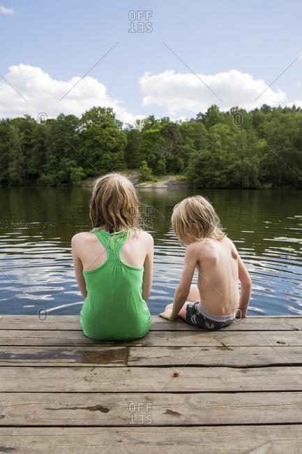 Sweden, Stockholm, Nacka, Sicklasjon, Lake Sickla, Rear view of children sitting on wooden jetty
