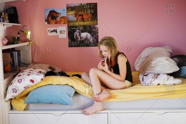Sweden, Girl texting in her bedroom