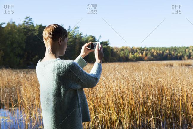 Sweden, Sodermanland, Nacka, Woman taking pictures of wetland