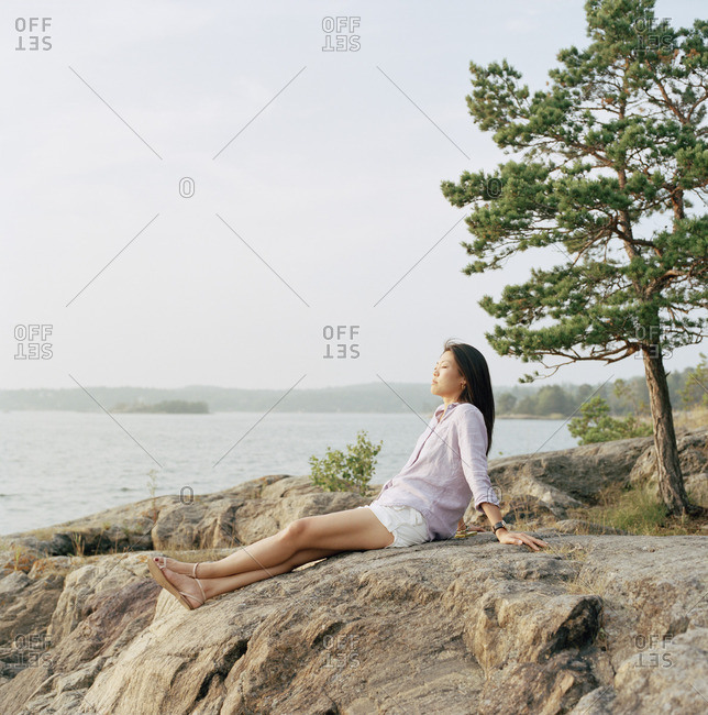Sweden, Stockholm Archipelago, Sodermanland, Nacka, Mid-adult woman relaxing on beach