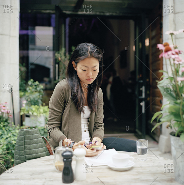 Sweden, Stockholm, Ostermalm, Woman sitting at sidewalk cafe and text messaging