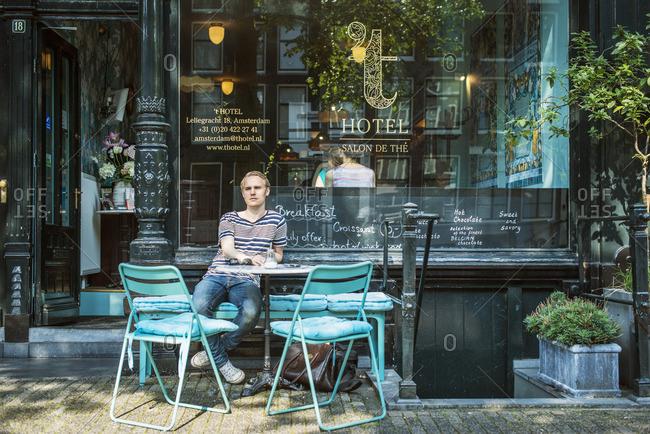 Netherlands, Amsterdam, Man sitting outside cafe
