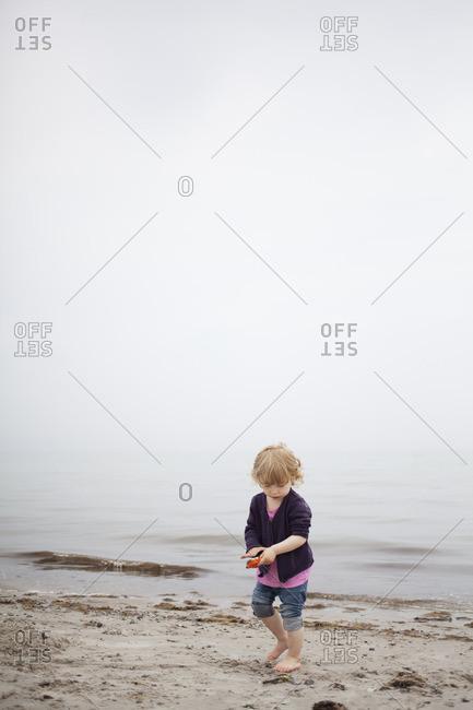 Sweden, Skane, Osterlen, Girl building with sand