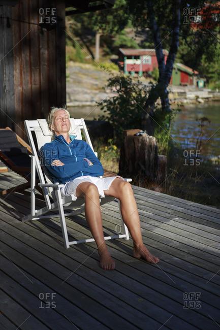 Sweden, Stockholm Archipelago, Sodermanland, Mefjard, Mature woman relaxing in deckchair