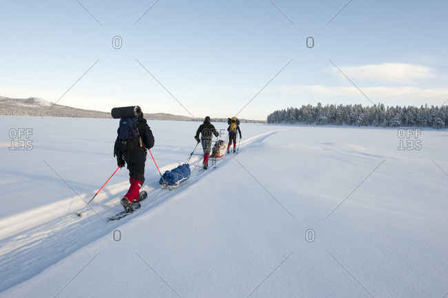 Sweden, Lappland, Jokkmokk, Three men cross-country skiing across frozen lake in winter