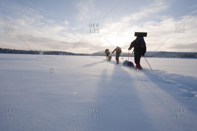 Sweden, Lappland, Jokkmokk, Three men cross-country skiing across frozen lake in winter