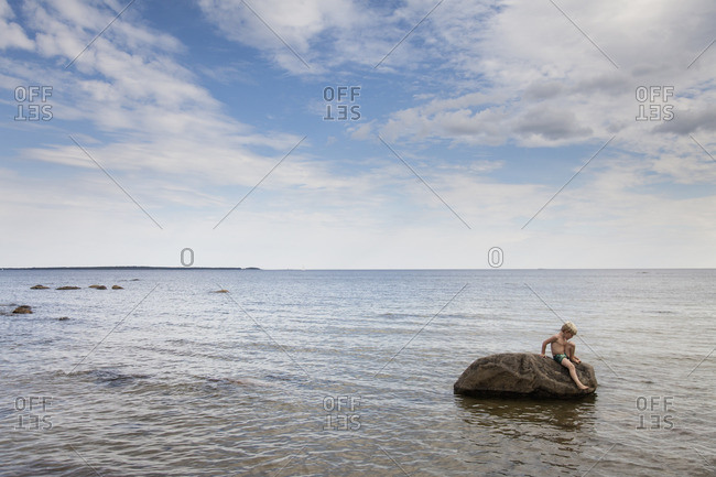 Sweden, Halsingland, Mellanfjarden, Boy sitting on rock