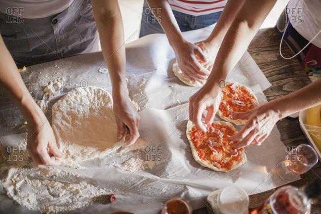 Italy, Tuscany, Women preparing homemade pizzas
