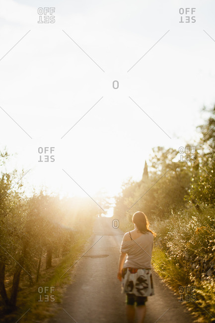 Italy, Tuscany, Rear view of woman walking on road