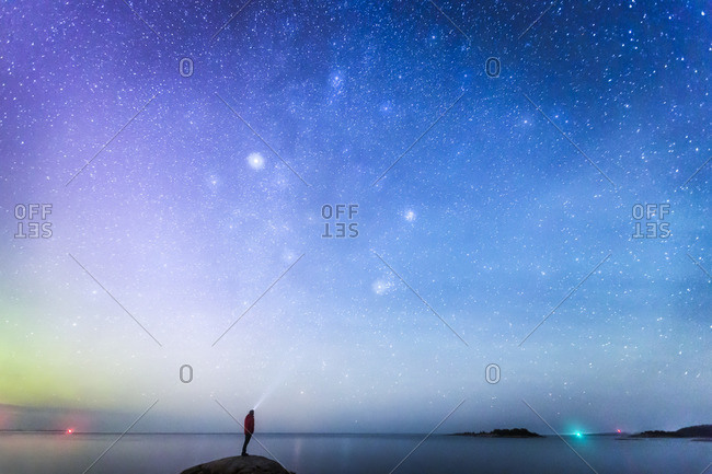 Sweden, Medelpad, Juniskar, Silhouette of man looking at night sky
