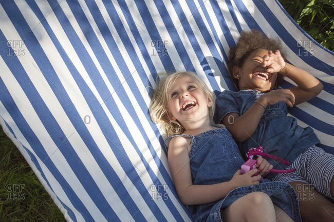 Sweden, Medelpad, Two girls lying in striped hammock and laughing