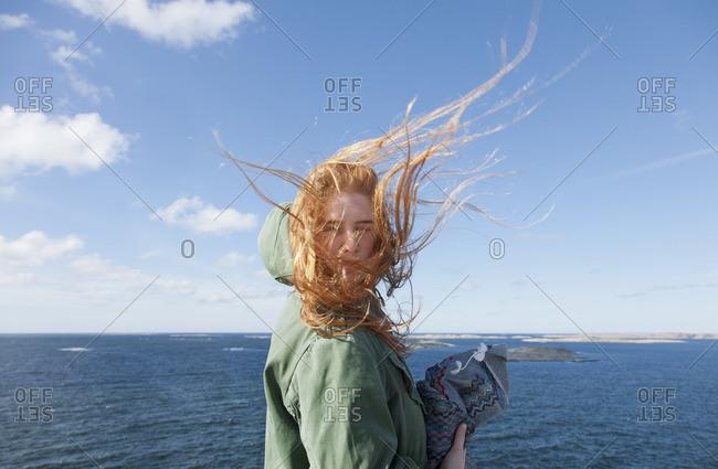 Sweden, Swedish West Coast, Bohuslan, Skaftolandet, Young woman standing at seaside