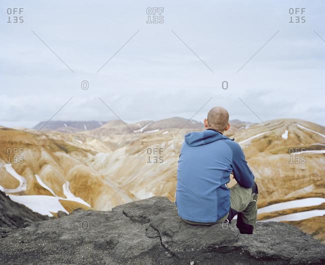 Iceland, Landmannalaugur, Man sitting on rock and looking at view