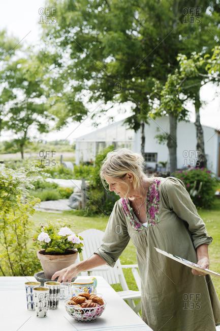 Sweden, Gotland, Bursvik, Burgegard, Senior woman preparing table
