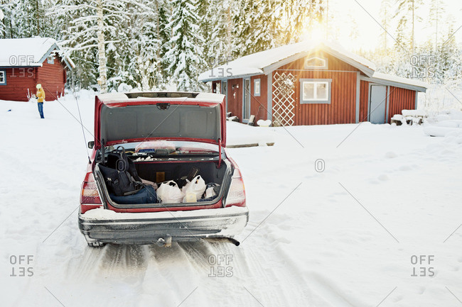 Sweden, Dalarna, Svardsjo, Rear view of car with opened trunk during winter