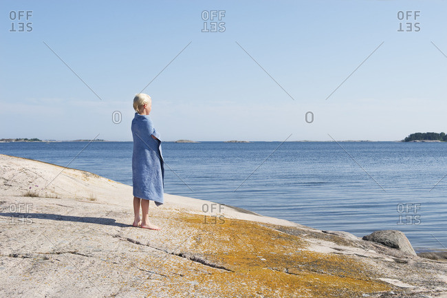 Sweden, Sodermanland, Stockholm Archipelago, Varmdo, Boy wrapped in towel standing on rocky beach