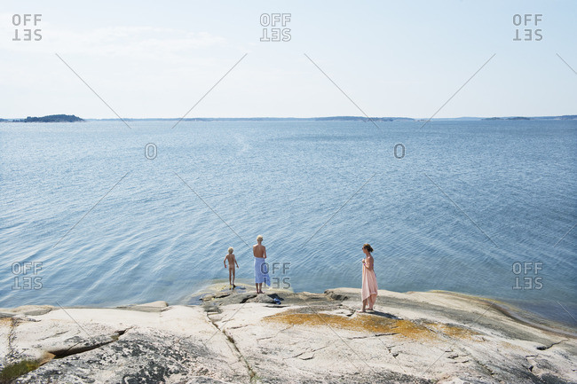 Sweden, Sodermanland, Stockholm Archipelago, Varmdo, Mother with sons on rocky beach at sunny day