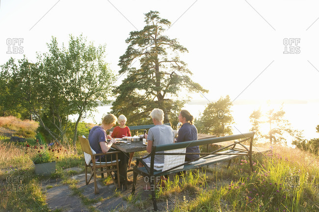 Sweden, Sodermanland, Stockholm Archipelago, Haninge, Dalaro, Family having dinner in garden