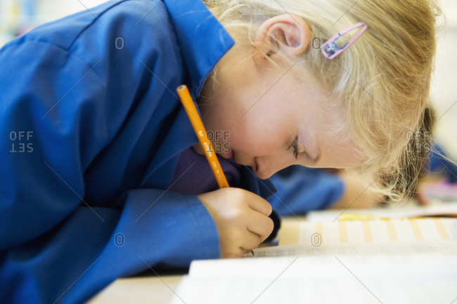 Sweden, Uppland, Norrmalm, Side view of girl writing in classroom