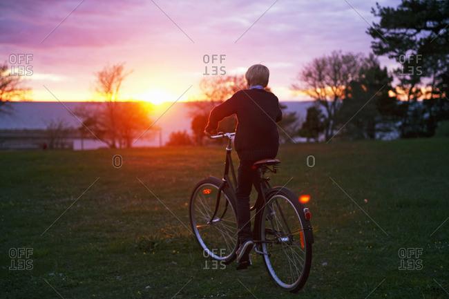 Sweden, Gotland, Djupvik, Boy cycling at sunset
