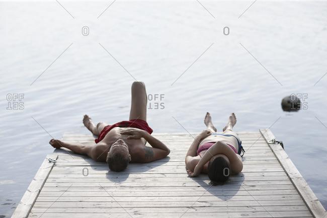 Sweden, Dalarna, Siljan, Man and woman lying on jetty