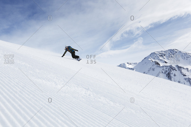 Switzerland, Andermatt, Young woman snowboarding in Alps