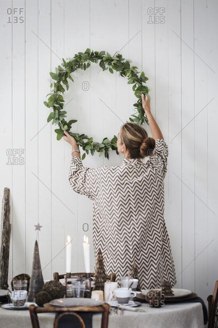 Sweden, Woman hanging Christmas wreath on wall