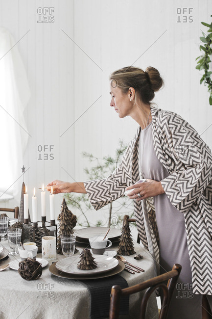 Sweden, Woman lighting candles during Christmas
