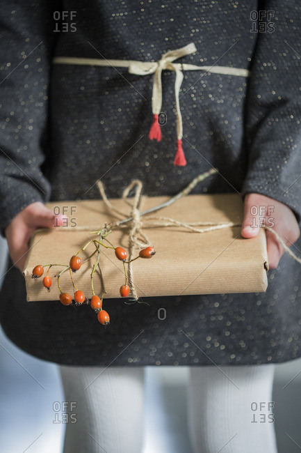 Sweden, Girl holding wrapped Christmas present