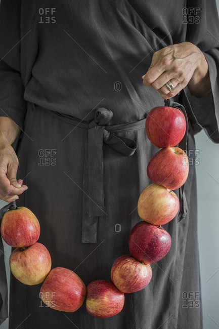 Sweden, Woman in grey dress standing holding apples tied up together