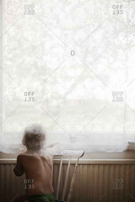 Sweden, Rear view of young boy looking through window
