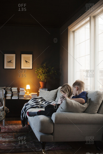 Denmark, Boy and girl sitting on sofa in living room