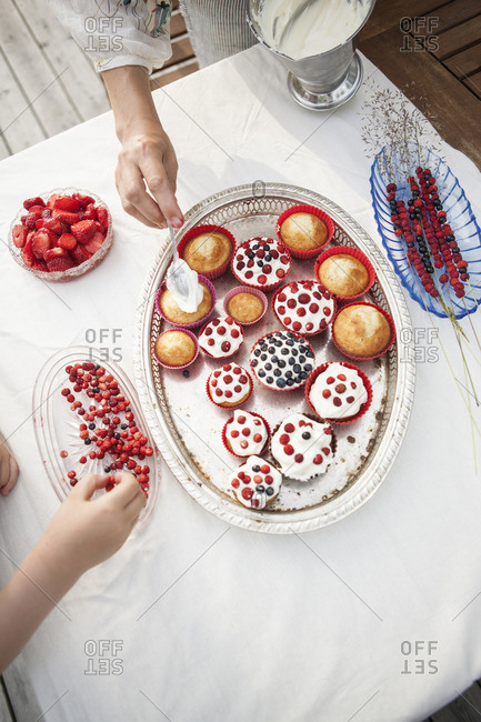 Sweden, Smaland, Mother and daughter decorating cupcakes