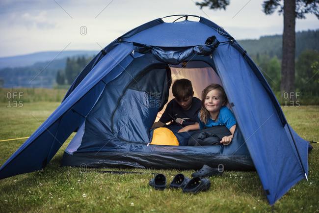Sweden, Dalarna, Salen, Children in tent in meadow