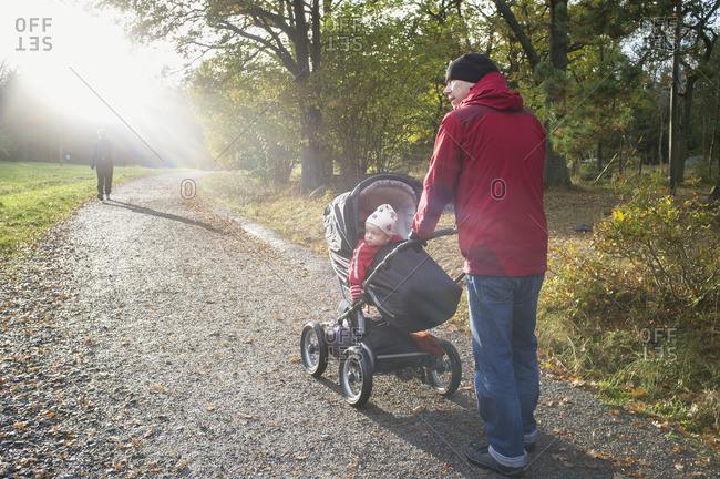 Sweden, Sodermanland, Nacka, man with son walking in park