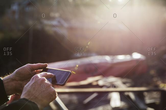 Sweden, Uppland, Rindo, Close-up of man using smart phone