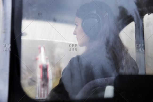 Sweden, Uppland, Nacka, Woman driving bulldozer