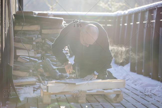 Sweden, Uppland, Man cutting wood with jigsaw
