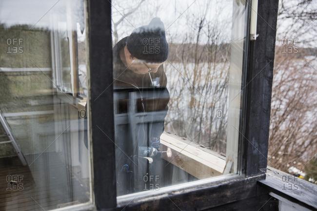 Sweden, Uppland, Rindo, Man building wooden balustrade