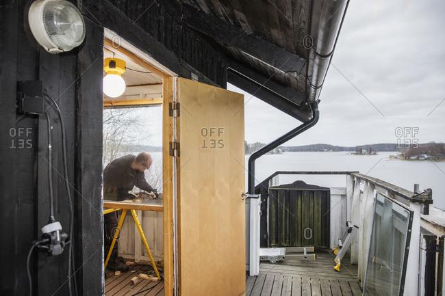 Sweden, Uppland, Stockholm archipelago, Rindo, Man building wooden balustrade