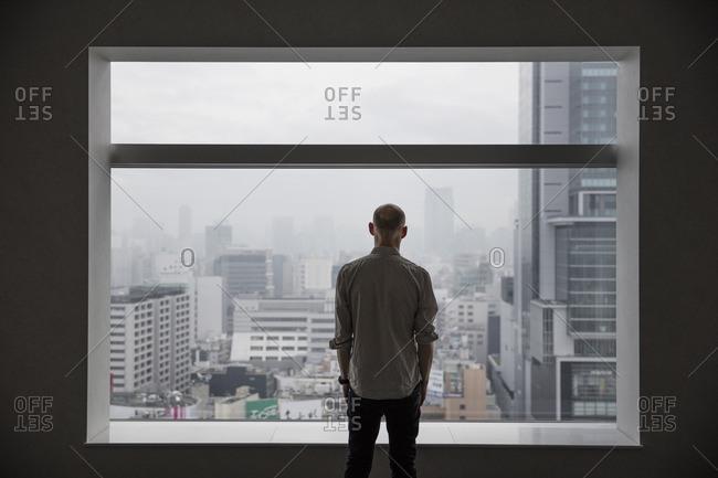 Japan, Tokyo, Shibuya, Man looking at cityscape through window