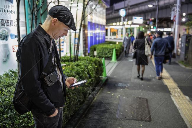 Japan, Tokyo, Shibuya, Man standing and using phone