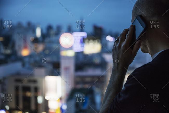 Japan, Tokyo, Shibuya, Man talking on phone and looking through window
