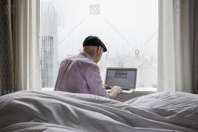 Japan, Tokyo, Shibuya, Man sitting on bed and using laptop