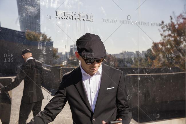 Japan, Tokyo, Shibuya, Man standing outside building, using phone