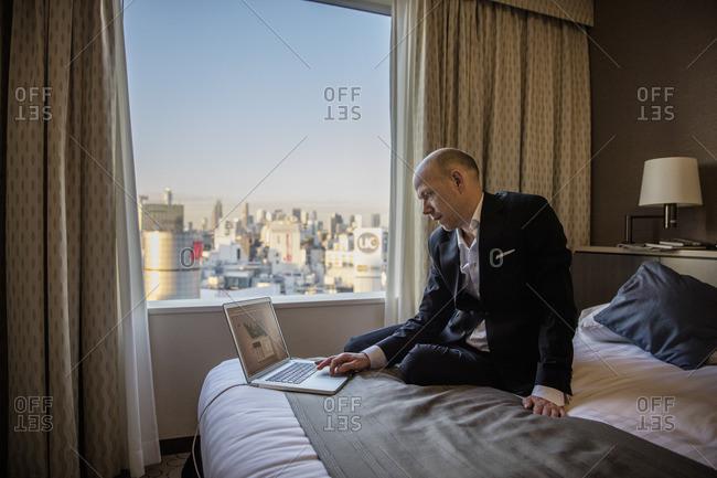 Japan, Tokyo, Shibuya, Businessman working in hotel room
