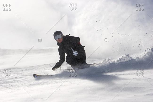 Switzerland, Andermatt, Woman skiing down slope in fresh snow