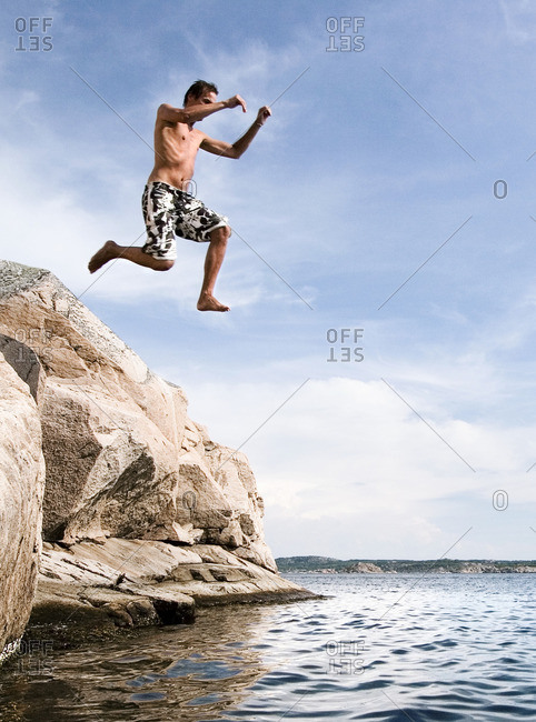 Sweden, Bohuslan, Tjorn, Man jumping into lake